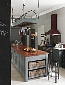 Grey-painted island counter below suspended wire rack of cooking utensils and transparent bar stool in kitchen