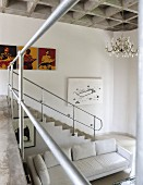 View from gallery of masonry staircase with metal balustrade of white sofa in open-plan interior with concrete coffered ceiling