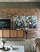 Designer sideboard against brick wall, modern artworks and white coffee table in living room