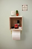 DIY shelf made from small wooden box with chain toilet roll holder below