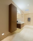 Floating cupboard and washstand with wooden fronts in designer bathroom painted beige