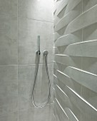 Modern, rod-shaped shower head mounted on marbled tiles in shower cubicle