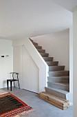 Beton-Treppenaufgang mit Holzschwelle und eingebautem Wandschrank im minimalistischen Designerstil
