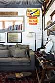 Corner of rustic room with white wood-clad walls, grey couch below pictures and vintage advertising panels and holiday souvenirs on wooden table to one side