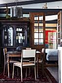 Retro Stühle um Holztisch vor antikem Schrank mit Vitrinen Aufsatz, seitlich offene Flügeltür