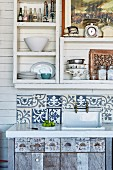 Rustic sink unit with wooden base cabinet and splashback made from Indonesian tiles below shelving on white, wood-clad wall