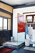 Rustic shower area with vintage advertising sign on glass screen in bathroom