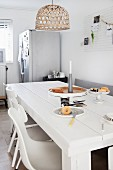 White-painted, solid wooden table below wicker lampshade in kitchen-dining room