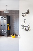 Grey-painted locker, patterned wallpaper, yellow plastic container of toys and boys names hung on door in boys' bedroom
