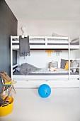 Reduziertes Jungenzimmer mit weißem Stockbett und grauer Tapete, dazu gelbe und blauer Farbakzent