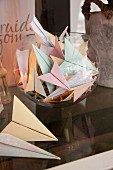 Paper planes in various pastel shades in glass container