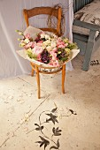 Bouquet of wooden chair next to floral motif painted on floor
