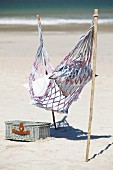 Hammock attached to sticks stuck in sandy beach next to picnic basket