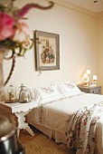 Floral bed linen, religious picture and ornaments under glass covers in romantic, vintage-style bedroom