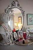 Family photos, perfume bottles and bust used as jewellery stand in front of ornate silver mirror on top of chest of drawers