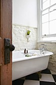 Bathroom with vintage free-standing bathtub against exposed stone wall