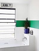 Badewanne vor Fenster mit Kippfenster in weißem Bad mit grünem Streifen