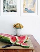Aufgeschnittene Wassermelone auf Schneidebrett und Blumenkrug auf Tisch unter gerahmten Zeichnungen