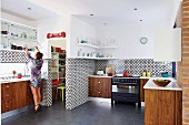 Wooden base units against black and white, geometric wall tiles and woman opening wall cabinet in open-plan kitchen