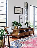 Stuhl mit hellbraunem Lederbezug neben Sideboard aus Massivholz, vor Wand mit gerahmten Bildern