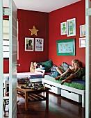 Kinder auf Betten im Kinderzimmer mit roten Wänden und aufgehängten Bildern