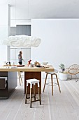 Bar stools around kitchen counter below designer pendant lamps in modern, open-plan interior with pale wooden floor