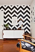 Sideboard with white sliding doors against wall covered in black and white geometric pattern
