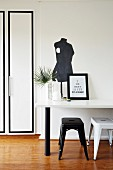 Black and white workspace with retro stools and table below silhouette of tailors' dummy painted on wall