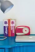 Retro radio, books and desk lamp on blue desk