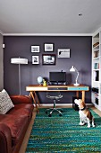 Desk with colourful drawer fronts and swivel chair with transparent shell seat in study with grey-painted wall and dog on rug in front of leather couch