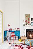Blau lackierter Schreibtisch und roter Stuhl in Zimmerecke neben Kamin