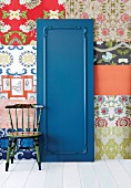 Blue-painted door with decorative moulding against wall covered in patchwork of different wallpapers