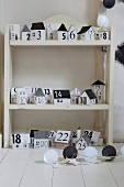 Advent calender made from black and white paper houses on shelves
