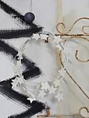 Kranz aus Papiersternen an Vintage-Gitter aufgehängt