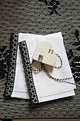 White linen napkin with black trim and wooden tag