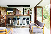 50s-style couch in lounge area in front of breakfast bar and retro bar stools in open-plan interior with folding glass doors leading to garden