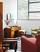 Comfortable armchair and wooden dressing table in corner below open pivot windows