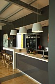 Pendant lamps above counter and breakfast bar with glossy fronts