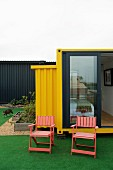 Garden chairs on artificial lawn in front of yellow shipping-container home