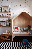 Child's cubby sofa, rocking deer and ornaments on shelves against walls with pattern of stencilled black triangles