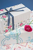Gifts wrapped in old, vintage-style table cloths decorated with cross-stitch embroidery