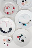 Necklaces made from colourful buttons and coloured cotton cords on plates
