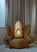Extravagant flower-shaped armchair with gold upholstery in front of floor-length curtain