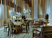 Chairs with gold upholstery around dining table below pendant lamps with lampshades made from stylised bamboo stems