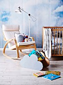Hand-crafted cloud-shaped magazine rack in front of rocking chair and standard lamp against wall painted with mural of cloudy sky