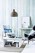 DIY coffee table painted white, comfortable armchairs and wall clad in vertical wooden boards