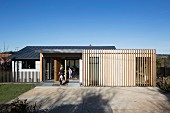 Blue sky above modern house with family in open front door and vertical wooden slat structure covering facade in rural area