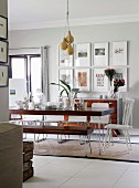 Dark wood table and bench set with metal frames and kitchen chair painted white at head of table in interior with vintage ambiance