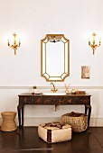 Antique, painted washstand and framed mirror flanked by candle sconces above pouffe and basket on dark floor