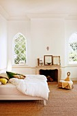 Double bed with white bed linen in traditional bedroom with sisal carpet and arched lattice windows